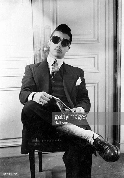 A man with a thin moustache and a quiff hairdo wearing a zoot style outfit in Paris 1944