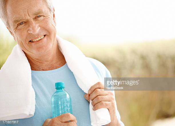 A man with a towel on his shoulders holding a water bottle