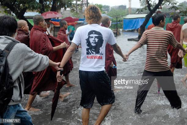 A man with a tshirt bearing a portrait of Che Guevara joins a human chain protecting Burmese Buddhist monks who are marching in the streets of...