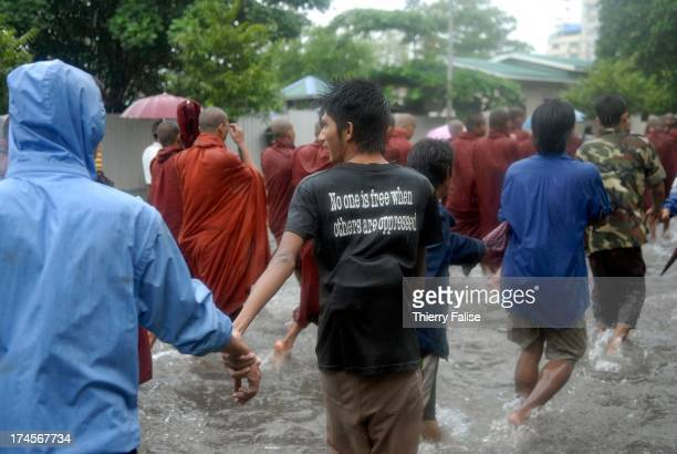 """Man with a t-shirt reading """"no one is free when others are oppressed"""" joins a human chain protecting Burmese Buddhist monks who are marching in the..."""