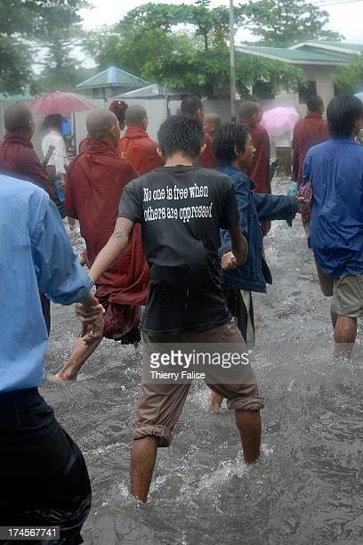 A man with a tshirt reading 'no one is free when others are oppressed' joins a human chain protecting Burmese Buddhist monks who are marching in the...