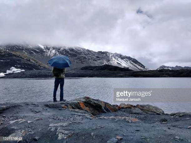 man with a umbrella looking at a lake and mountains covered with snow - 氷河湖 ストックフォトと画像