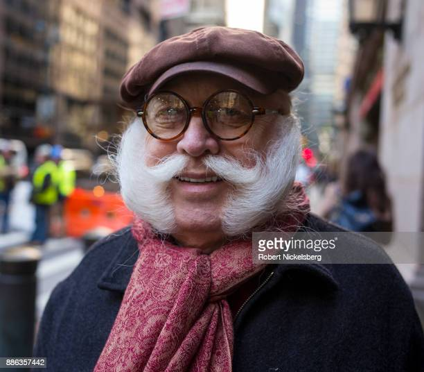 A man with a well groomed set of pork chop sideburns and mustache walks by Grand Central Station in New York City New York November 28 2017