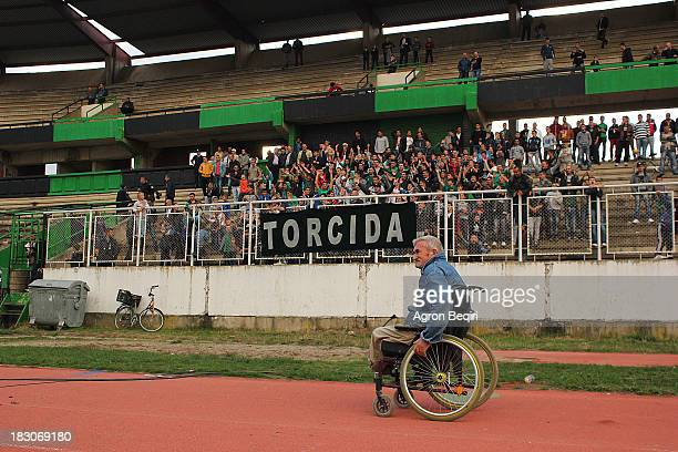 CONTENT] A man with a wheelchair passing near TORCIDA fans during a football match in Mitrovica Kosovo