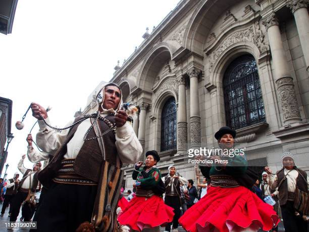 Man with a whip and a troup of dancers wearing a traditional costume as part of the Virgin of Candelaria launching festival parade in the main...