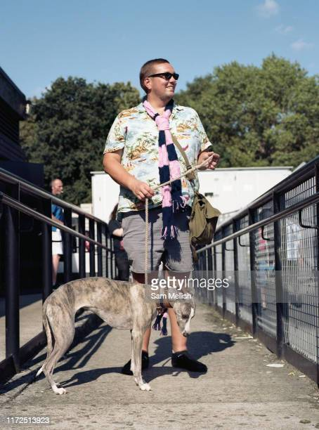 A man with a whippet dog during the Dulwich Hamlet Vs Hampton Richmond Borough game on the 1st September 2018 at the KNK Stadium in South London in...