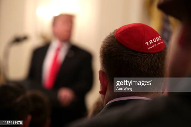A man with a yarmulke listens to US President Donald Trump during an East Room event at the White House March 21 2019 in Washington DC President...