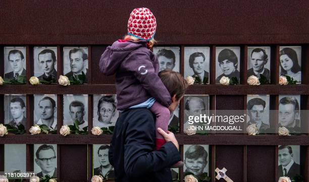 Man with a youg girl on his shoulders walks past the Berlin Wall memorial where flowers are placed in front of portraits of people who died trying to...