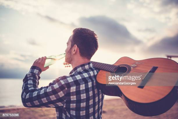 man with acoustic guitar and drinking beer looking the beach sunrise - guitarist stock pictures, royalty-free photos & images
