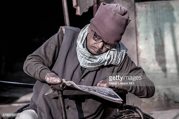 CONTENT] A man with advanced leprosy hands without fingers reading newspaper wears hat glasses sits on a wheel bicycle Monkey Temple Varanasi INDIA