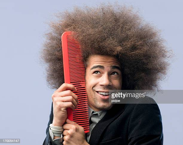 man with afro hair holding red comb to his face