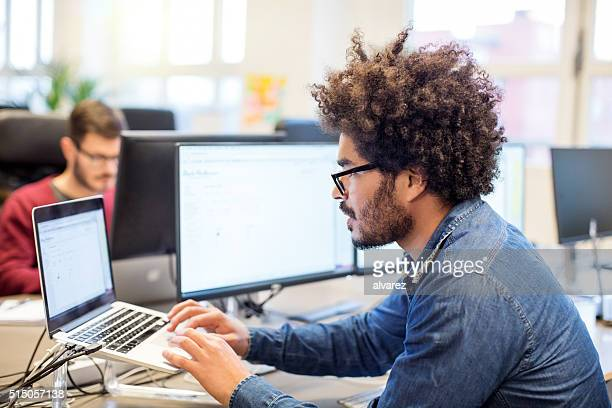 man with afro hairstyle working at his desk - science and technology stock pictures, royalty-free photos & images