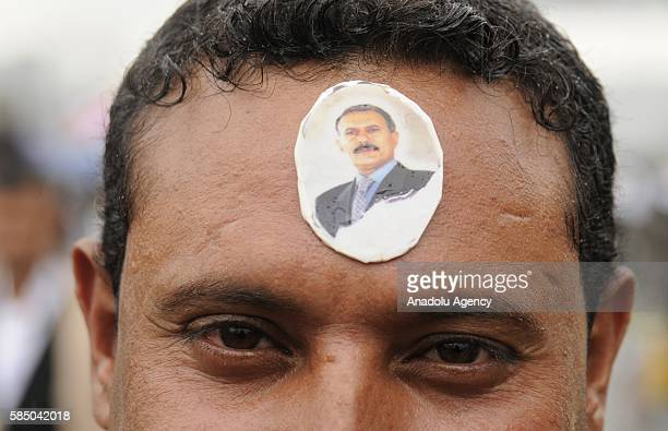 A man with Ali Abdullah Saleh's sticker on his forehead is seen as people gather to support the 'supreme council' which was established for state...