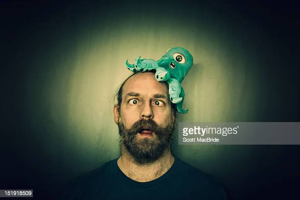 man with alien on head - scott macbride stock pictures, royalty-free photos & images