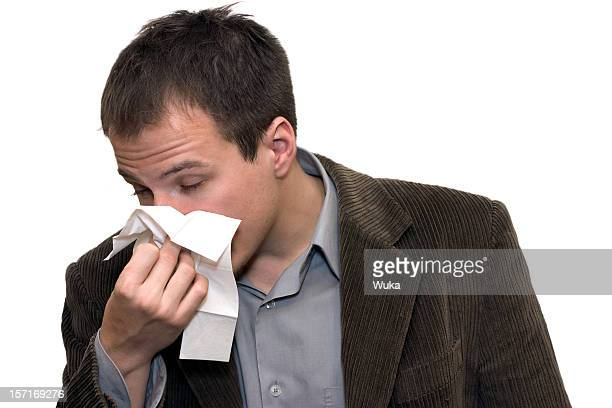 Man with allergies blowing nose on tissue