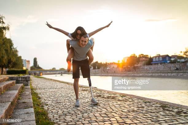 mann mit amputierten bein trägt freundinnen auf dem rücken - amputee woman stock-fotos und bilder