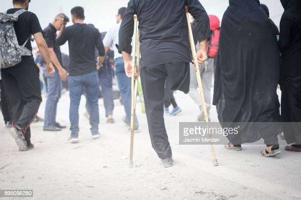 man with amputee leg walking between people - arbaeen fotografías e imágenes de stock