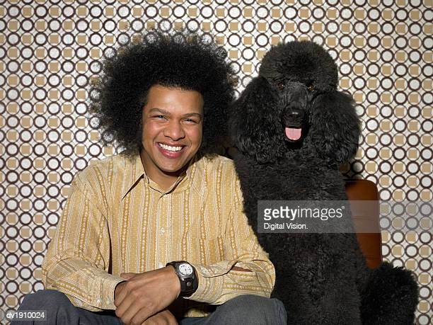 man with an afro sitting next to a black poodle - descrever imagens e fotografias de stock