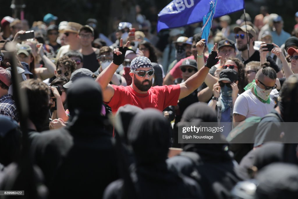 A man with an American flag bandana on his head makes the peace sign with his hands after being surrounded by black-clad protesters at MLK Jr. Park on August 27, 2017 in Berkeley, California. The park became a center of left-wing protest when hundreds of people opposed to President Trump and hundreds more aligned with Antifa descended on it after a planned right-wing rally was cancelled.
