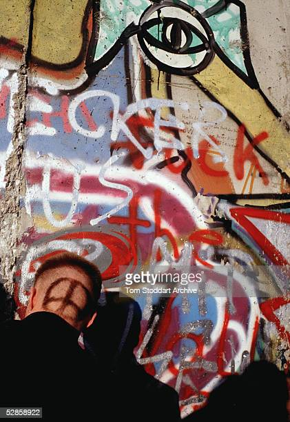 A man with an antiwar symbol dyed into his hair pictured at the Berlin Wall on the day the first section was opened
