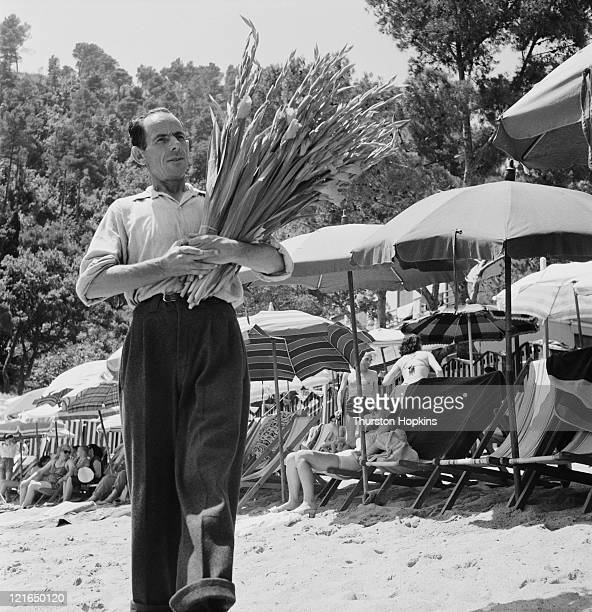 A man with an armful of flowers on Paraggi Beach near the tourist resort of Portofino Italy August 1952 Original Publication Picture Post 6023 unpub