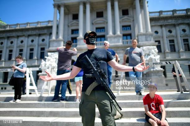A man with an assault rifle reacts while joining demonstrators outside the Pennsylvania Capitol Building to protest the continued closure of...