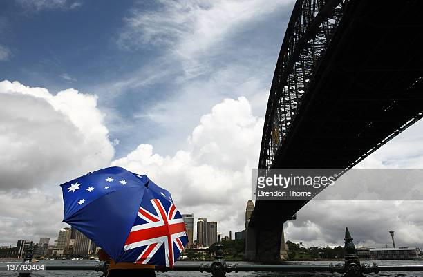 A man with an Australian themed umbrella stands in front of the Sydney Harbour Bridge as part of celebrations for Australia Day on January 26 2012 in...