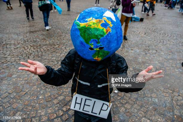 A man with an earth ball on his head makes gestures during the performance Before the International Extinction Rebellion week starts in Amsterdam a...