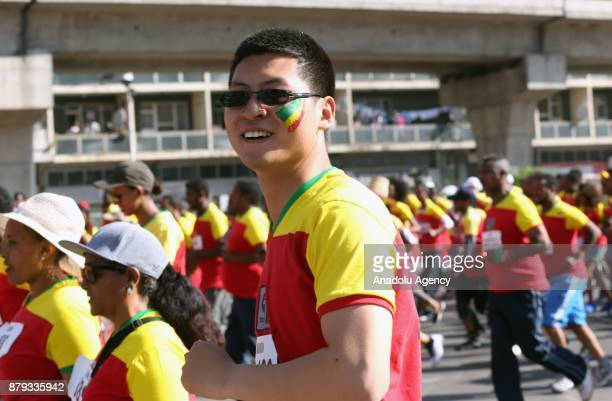 A man with an Ethiopian flag painted on his cheek attends the Great Ethiopian Run at Adwa Square in Addis Ababa Ethiopia on November 26 2017 Total of...
