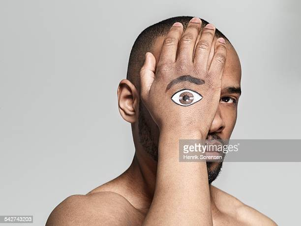 Man with an eye painted on his hand