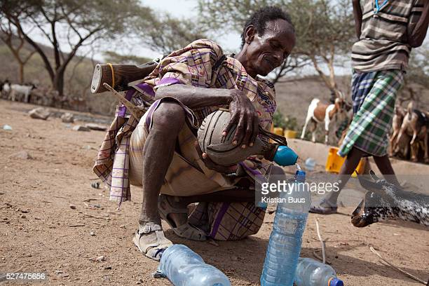 A man with an old AK47 on his back collect water from a water point The gun is to protect his livestock from wild animals and rustlers from other...
