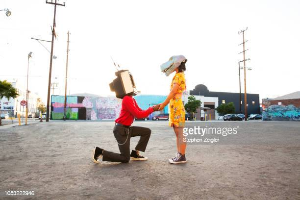 man with an old tv set over his head proposing to a woman wearing a dinosaur mask - fidanzato foto e immagini stock