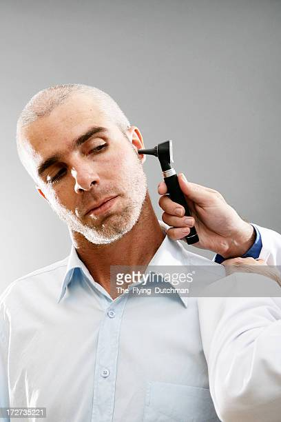 Man with an otoscope in his ear having a medical exam