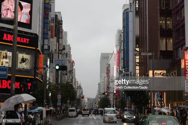 Man with an umbrella and pollution mask crosses an intersection on a rainy day in the Shinjuku ward, the center ward of Tokyo and the location of...