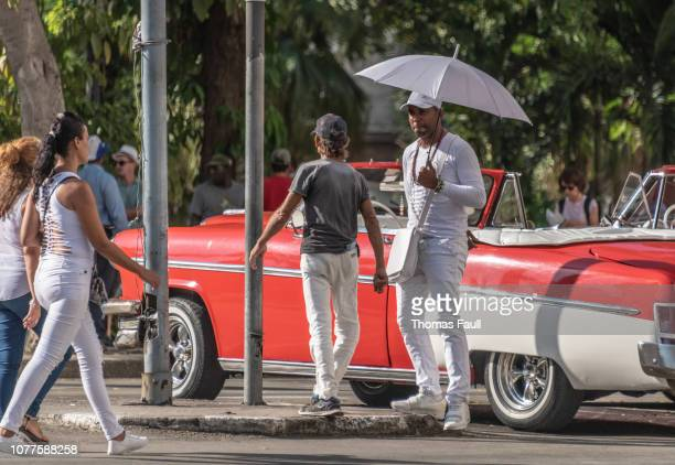 Man with an umbrella by a classic car in Havana