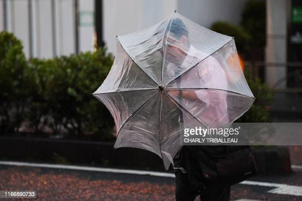 A man with an umbrella crosses a street early morning under the rain as a typhoon hits Tokyo on September 9 2019 A strong typhoon that could bring...