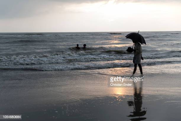 Cox´s Bazar Bangladesh October 14 2018 A man with an umbrella in his hand walks on the beach at sunset The beach of Cox's Bazar wIth 120 km long...