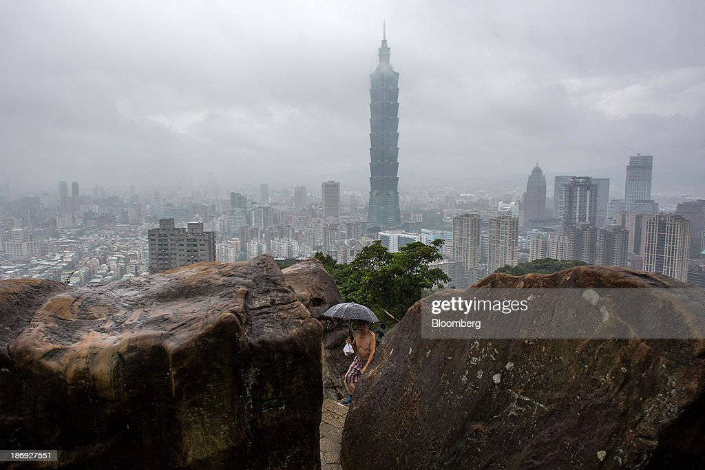 A man with an umbrella walks between rocks as the Taipei 101 building, center, stands among residential and commercial buildings in the background in Taipei, Taiwan, on Monday, Nov. 4, 2013. Taiwans five-year bonds gained for the first time in four days, lowering the yield from a three-week high, after a report showed inflation cooled. The local dollar strengthened. Photographer: Lam Yik Fei/Bloomberg via Getty Images
