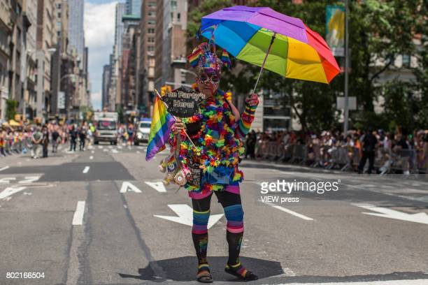 A man with an umbrella walks down Fifth Avenue during the annual New York Gay Pride Parade on June 25 2017 in New York City