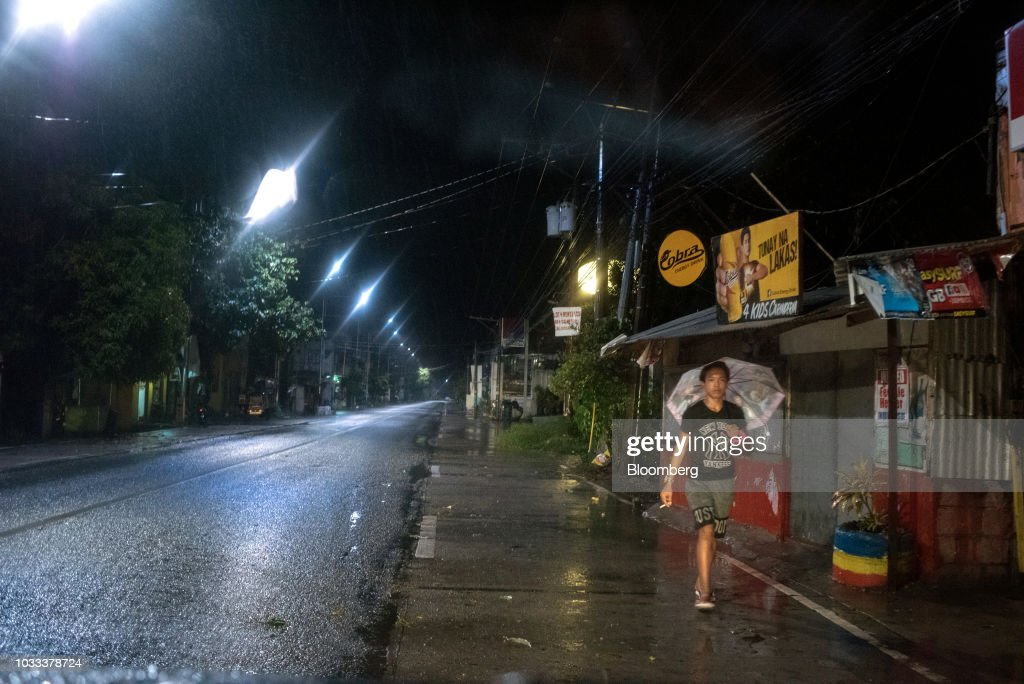 A man with an umbrella walks during heavy rainfall ahead of Typhoon Mangkhut's arrival in Tuguegarao, Cagayan province, the Philippines, on Friday, Sept. 14, 2018. Super Typhoon Mangkhut is expected to threaten Chinas Guangdong coastline, and Hong Kong, with a possible direct strike that may cause as much as $120 billion in damage and economic losses. Photographer: Carlo Gabuco/Bloomberg via Getty Images