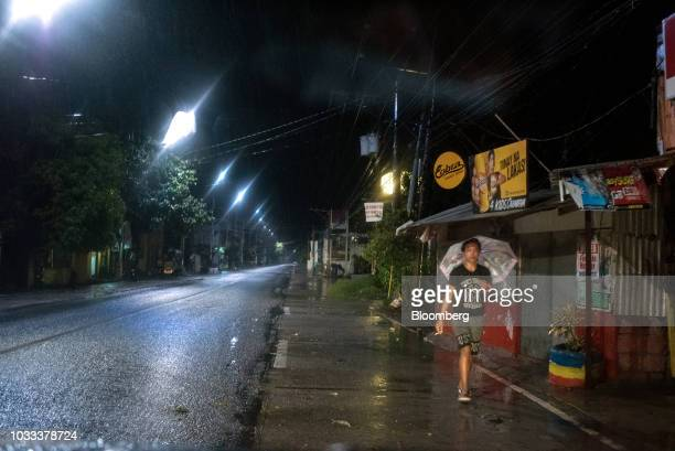 A man with an umbrella walks during heavy rainfall ahead of Typhoon Mangkhut's arrival in Tuguegarao Cagayan province the Philippines on Friday Sept...