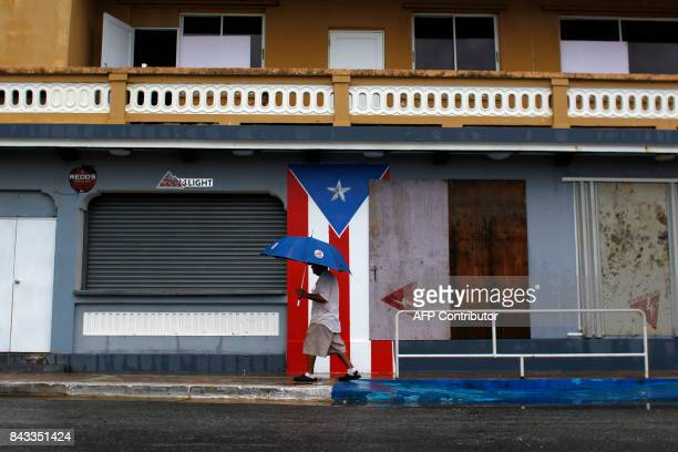 A man with an umbrella walks on a sidewalk as Hurricane Irma approaches Puerto Rico in Luquillo on September 6 2017 Irma is expected to reach the...