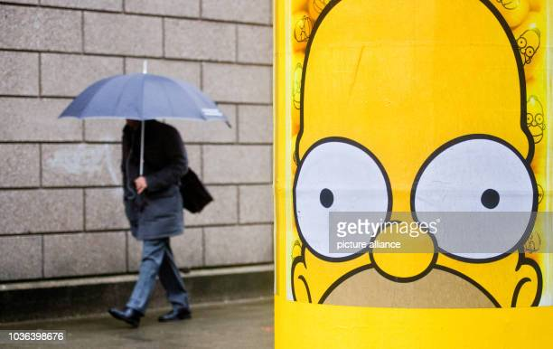 A man with an umbrella walks past a pillar with the cartoon character Homer Simpson from the cartoon series The Simpsons in Hanover Germany 07...