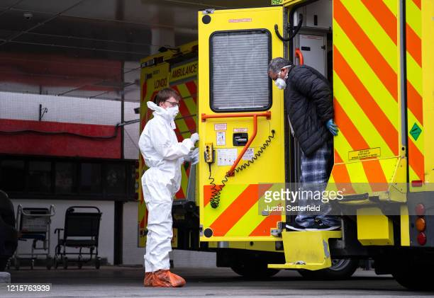 Man with an unknown condition is helped from an ambulance at the St Thomas' Hospital on March 30, 2020 in London, England. Hospitals across London...