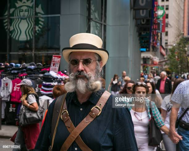 A man with an unusual handlebar moustache walks through Times Square on June 10 2017 in New York City With a full schedule of conventions and major...