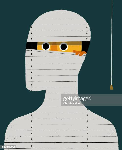 Man with anxiety peeking through blinds
