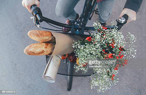 Man with apples, bouquet of flowers, newspaper and baguettes in bicycle basket