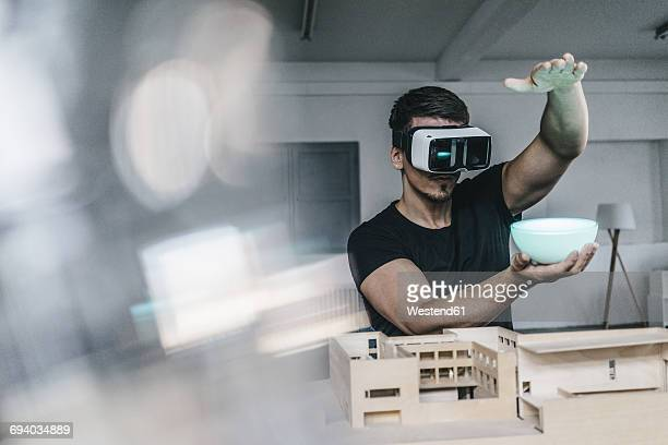 Man with architectural model and VR glasses holding bowl