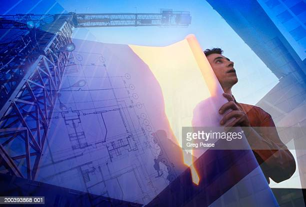 Man with architectural plans at construction site (digital composite)