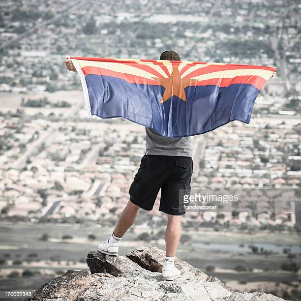 Man with arizona flag against phoenix panorama